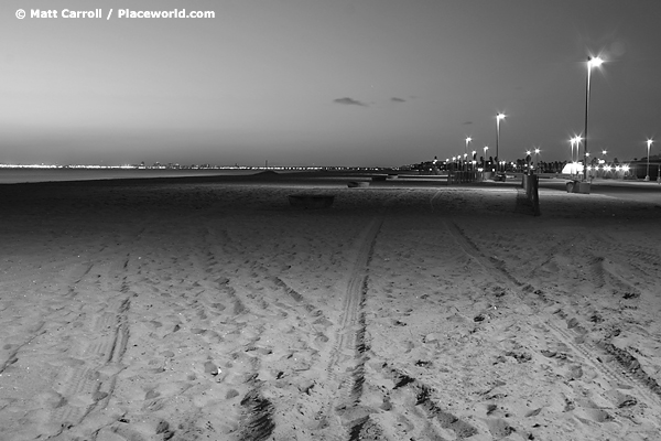 black and white illuminated beach at night looking toward Long Beach skyline
