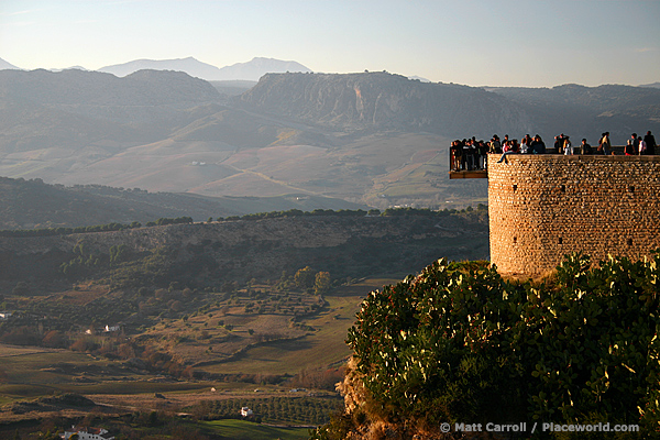 View of rugged countryside from cliff at Ronda, Spain. There is a viewing platform over edge of cliff full of people.